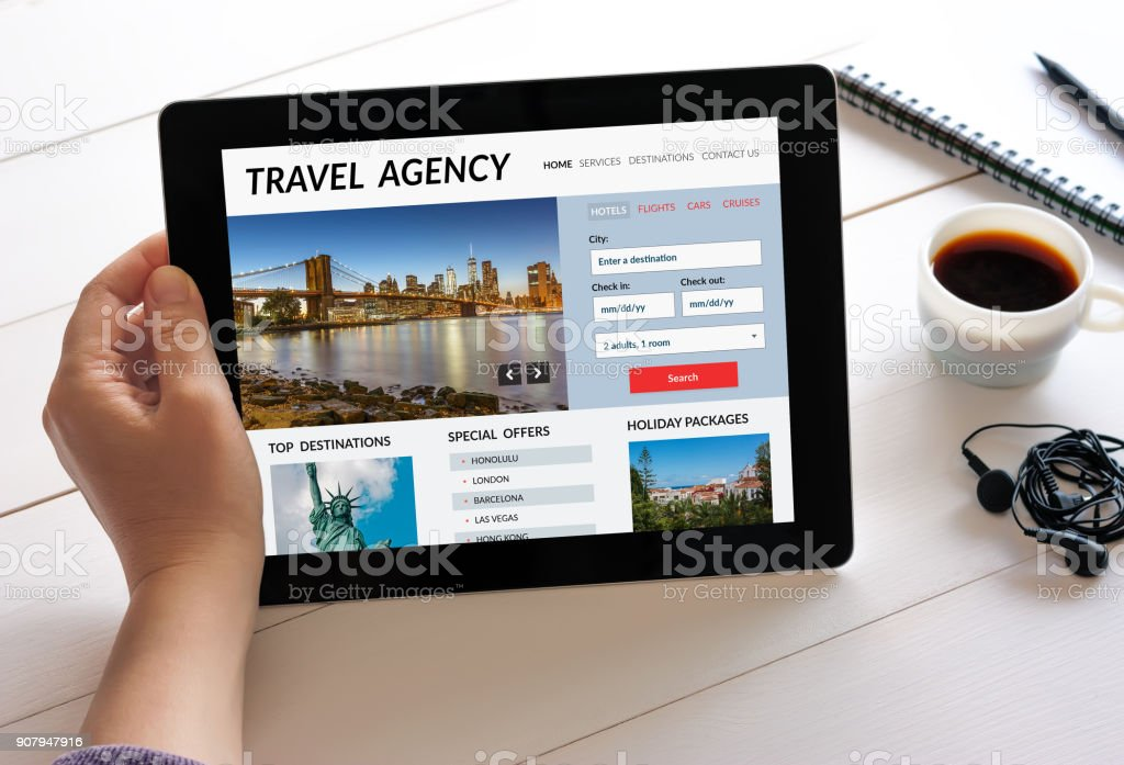 Hand holding tablet with travel agency concept on screen stock photo