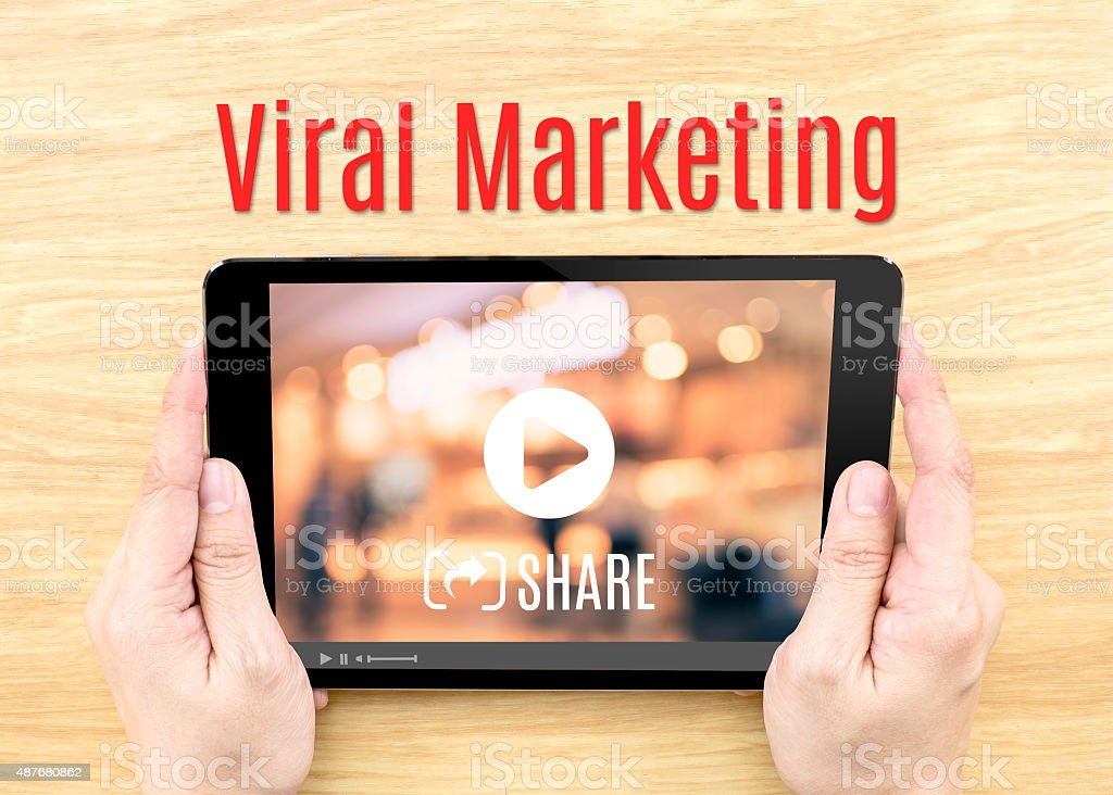 Hand holding tablet with Viral marketing word on wood table stock photo