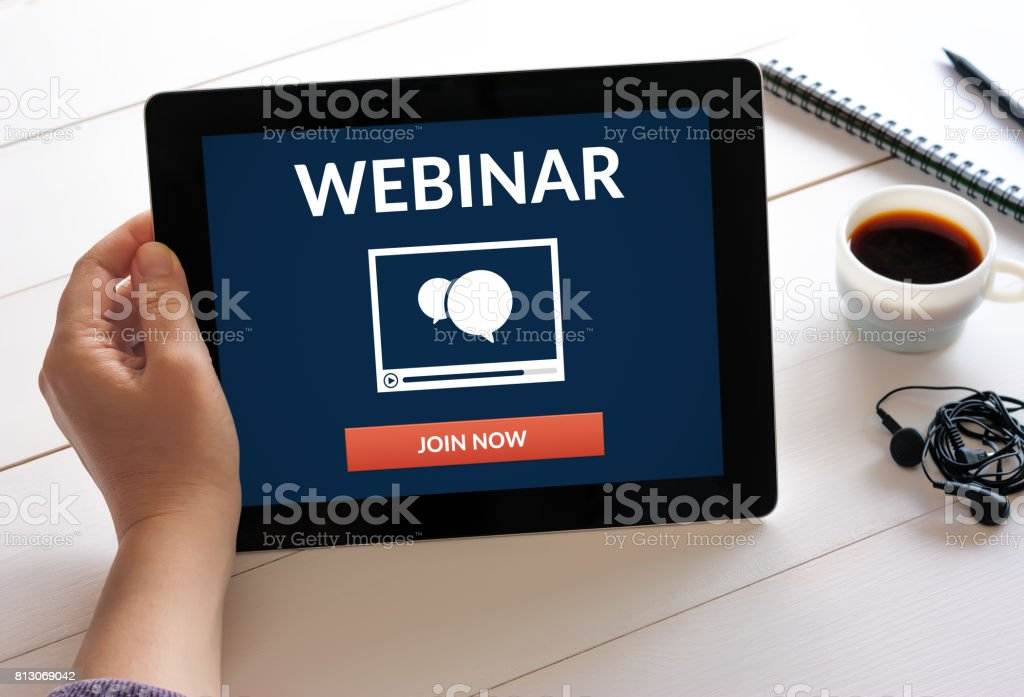 Hand holding tablet with webinar concept on screen stock photo