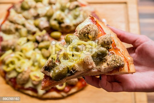 Female hand picking pizza slice, Hot Homemade Pepperoni, hamd and cheese Pizza, Slice of pizza margarita lifted up, hand holding tasty flavorful pizza