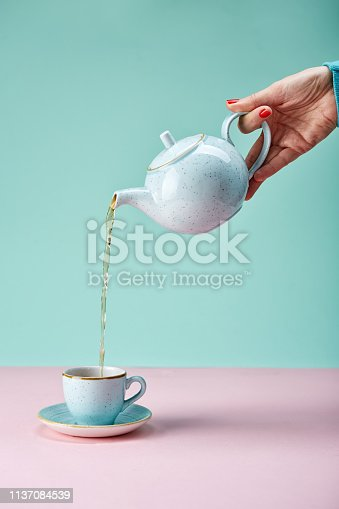 Tea pot pouring tea in a cup on blue backdrop
