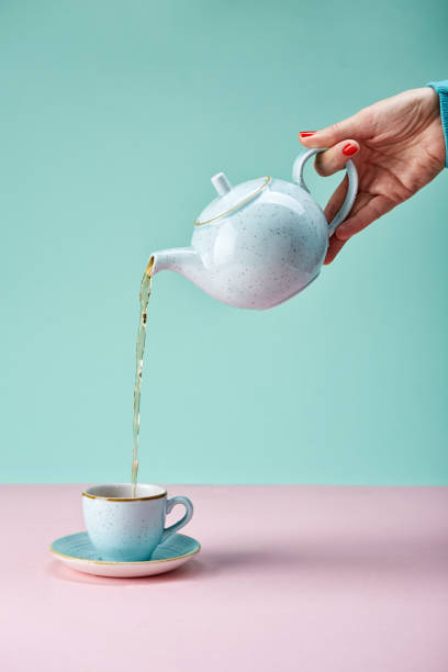 hand holding tea pot Tea pot pouring tea in a cup on blue backdrop teapot stock pictures, royalty-free photos & images