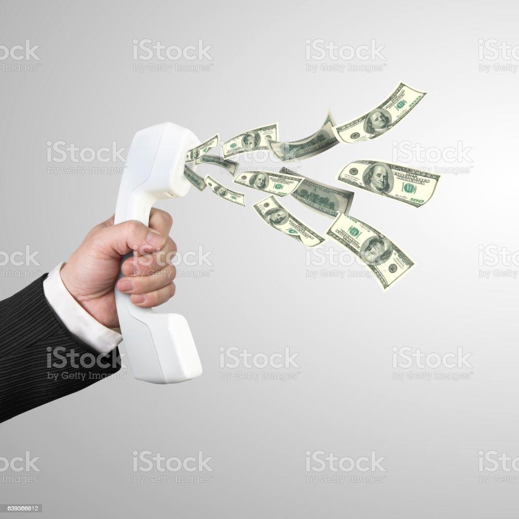 Hand holding telephone handset with money spraying out stock photo