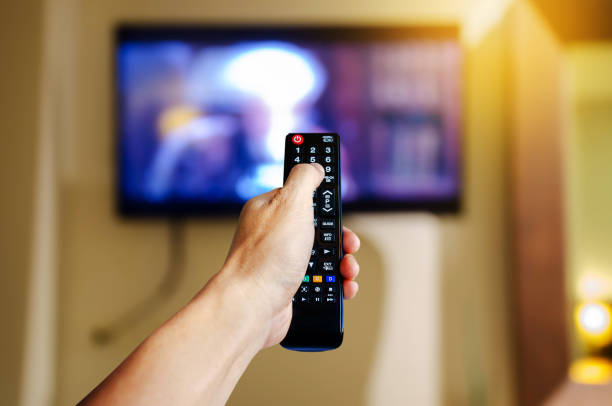 Hand holding television and audio multimedia remote control for watching tv Hand holding television and audio multimedia remote control for watching tv changing channels stock pictures, royalty-free photos & images