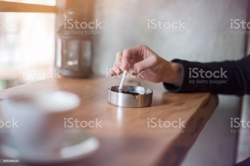 Mão segurando o cigarro no cinzeiro - foto de acervo