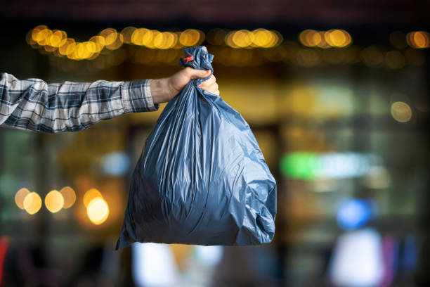 hand holding the  dark blue trash bag, concept of cleaning earth planet stock photo