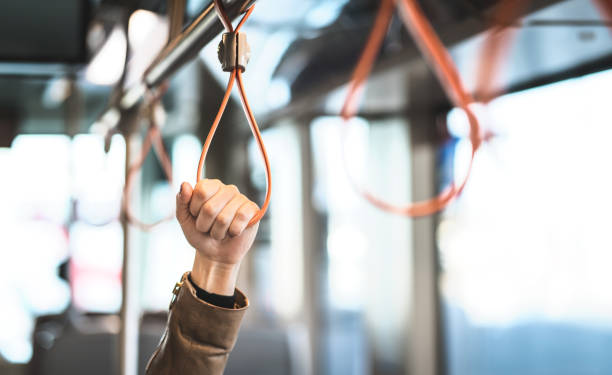 Hand holding the handle in tram, train, bus or subway. Passenger standing in public transportation. Person commuting. stock photo