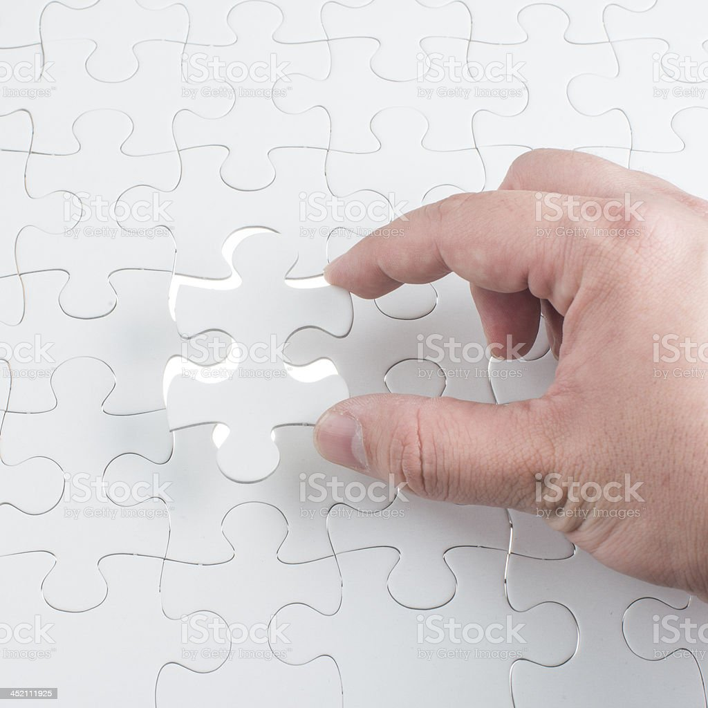 Hand holding the last piece of jigsaw puzzle royalty-free stock photo