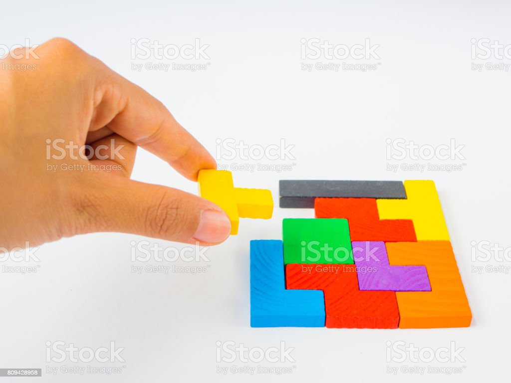 hand holding the last piece to complete a square tangram puzzle colorful wooden puzzle for kid on white background stock photo