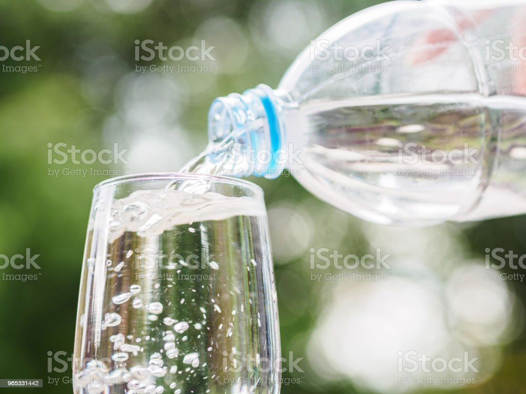 Hand holding the plastic bottle of water and pouring water into the glass on bokeh background royalty-free stock photo