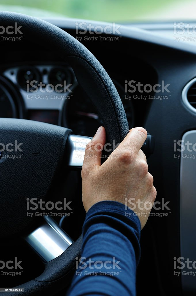 A hand holding the steering wheel royalty-free stock photo