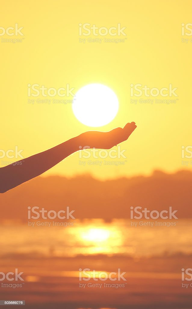 Hand holding the sun at sunset stock photo