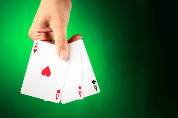 A hand holding three aces against a green background with copy space stock photo