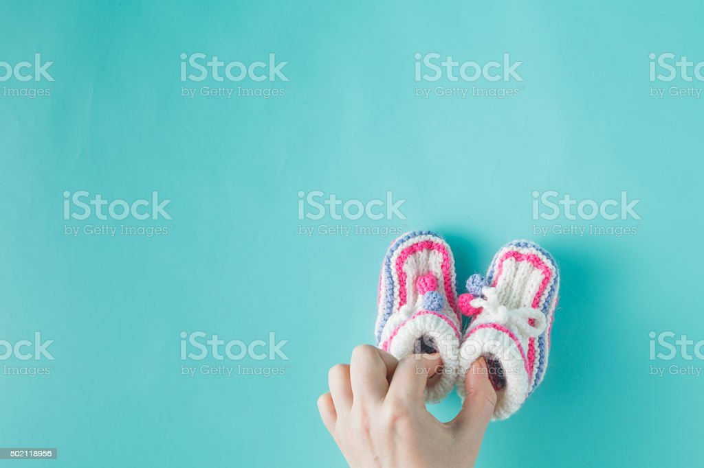 Hand holding tiny knitted booties stock photo