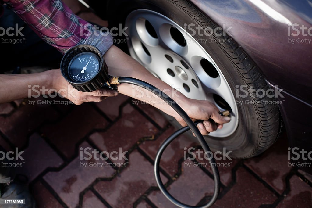 Hand holding tire pressure gauge attached to tire royalty-free stock photo