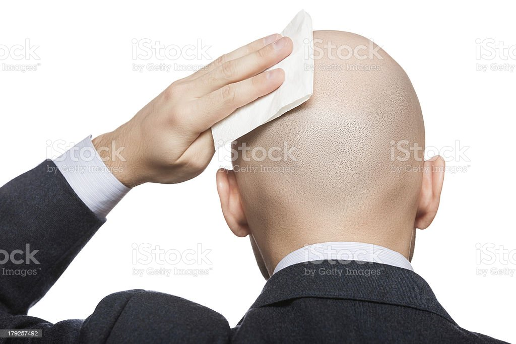 Hand holding tissue wiping or drying bald sweat head stock photo