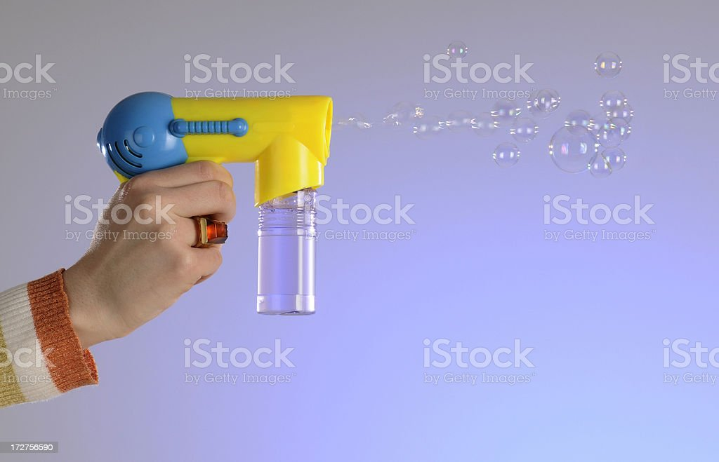 Hand Holding Toy Bubble Squirt Gun Stock Background stock photo