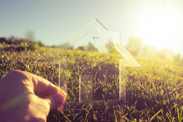 hand holding transparent house symbol in green field against the sun - estate agent sign stock photos and pictures