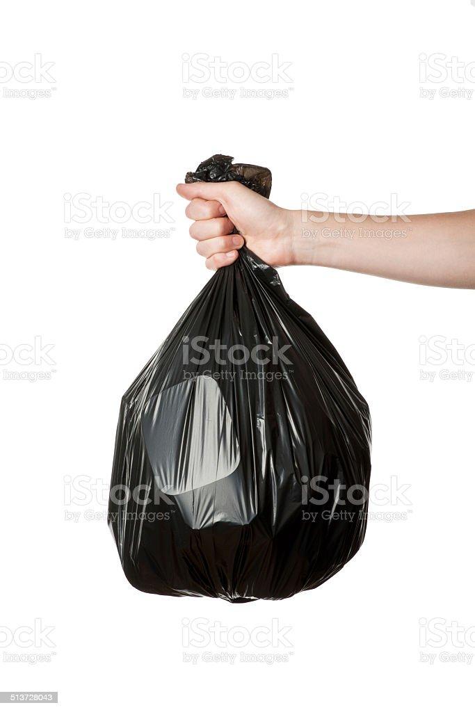 Hand holding trash bag stock photo