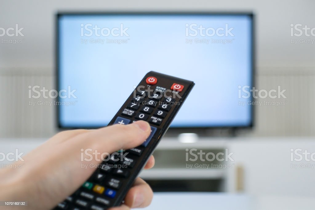 Hand holding TV remote control in front of blurred TV background