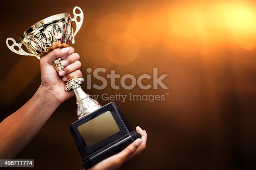 istock hand holding up a gold trophy 498711774