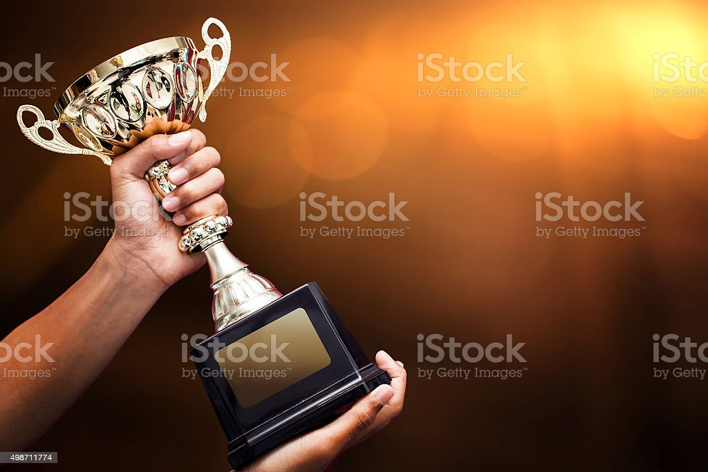 hand holding up a gold trophy stock photo