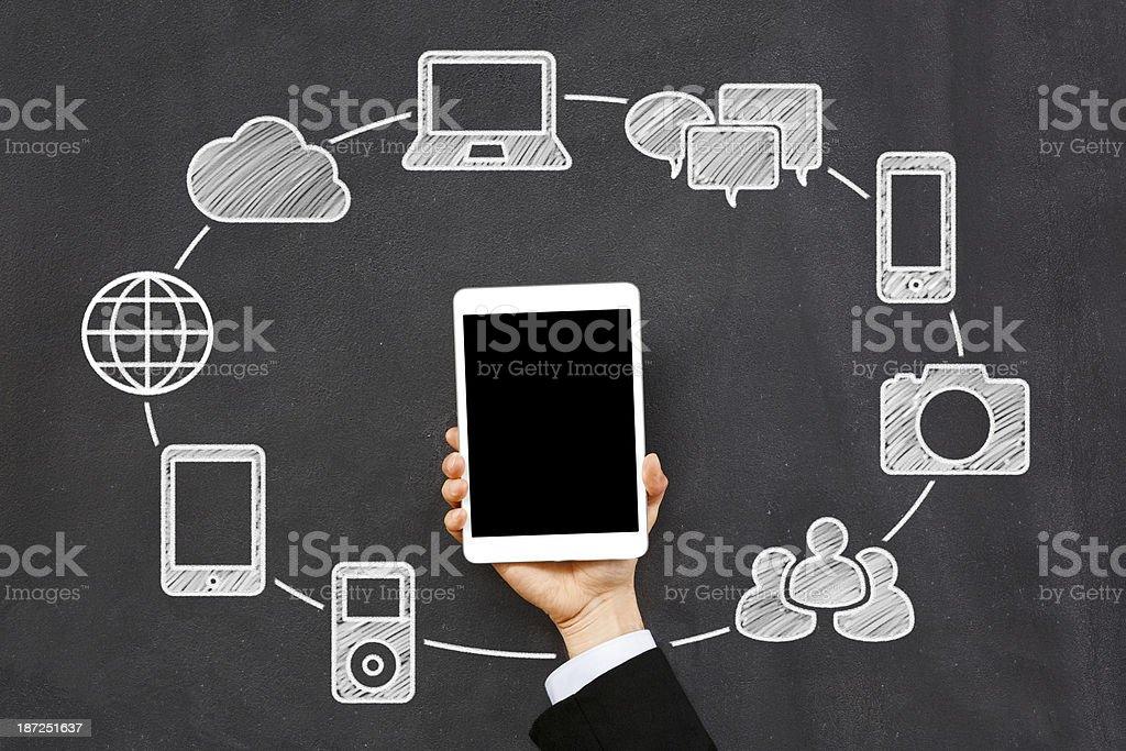 A hand holding up a tablet with network icons on a board royalty-free stock photo