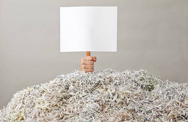 hand holding up blank sign under mountain of shredded paper - shredded paper stock photos and pictures