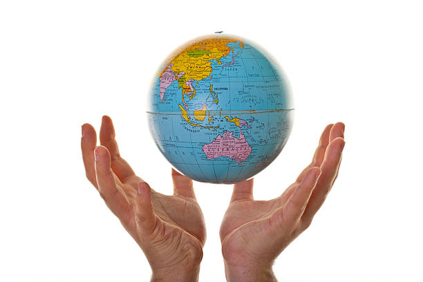 Hand holding up globe stock photo