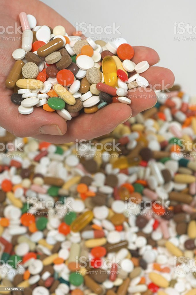 hand holding up pills/tablets stock photo