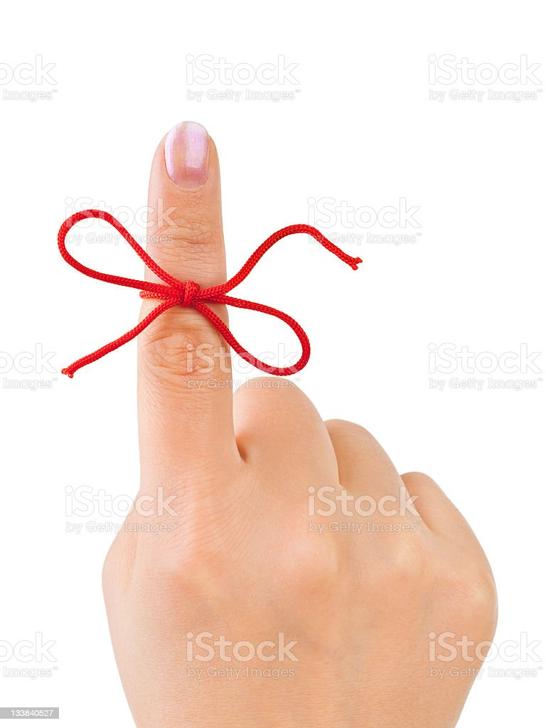 Hand holding up pointer finger with red bow tied on it stock photo