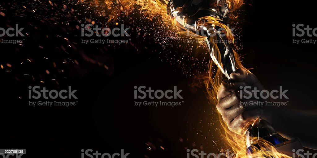 Hand holding up trophy goblet. Winner. Fire and energy stock photo