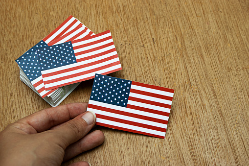 hand holding USA flag cards. For 4th of July, Memorial Day, Veteran's Day, or other patriotic celebration