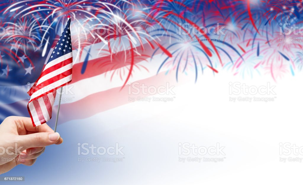 Hand holding USA flag on fireworks background stock photo