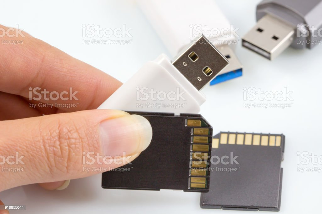 Hand holding usb stick, usb flash drive and memory card on white...