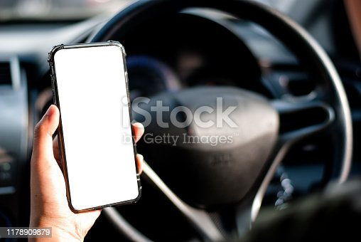 istock hand holding use smartphone new model, For searching for directions, in the latest car models.Concept of using a car phone. 1178909879