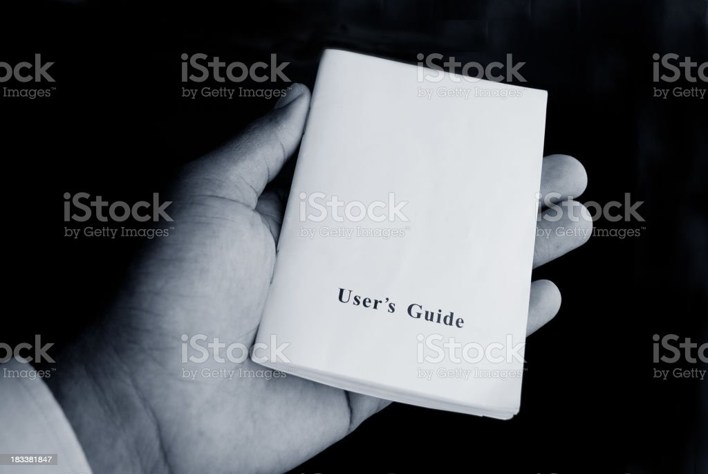 hand holding user's guide in monochrome stock photo