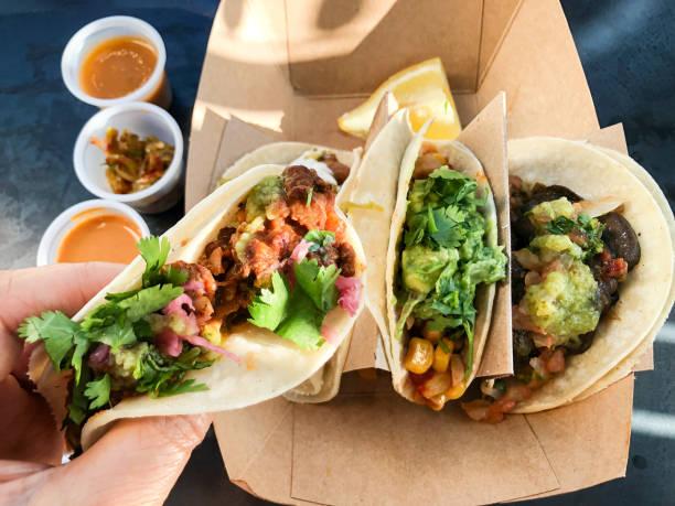pov de hand holding taco vegano sobre salsas y pepinillos - vegana fotografías e imágenes de stock