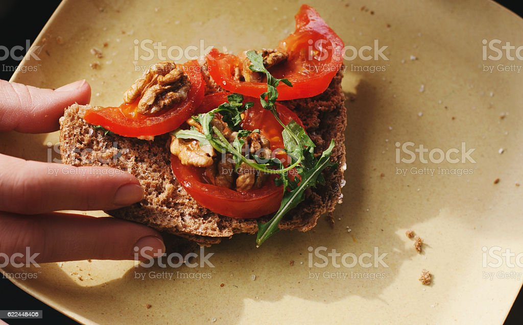 Hand holding veggie sandwich on a plate. Copy space. stock photo