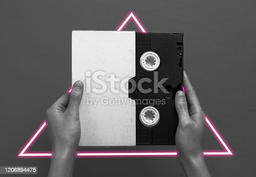 istock Hand holding video cassette. 80's synth wave and retrowave glowing triangle futuristic aesthetics. Old fashioned abstraction concept 1206894475