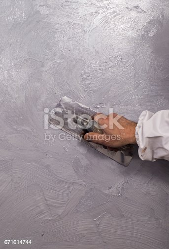 istock Hand holding wall tool,spring home decoration 671614744