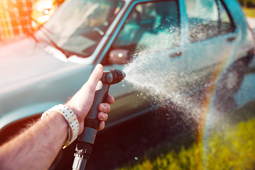 Hand holding water spray, washing car home concept