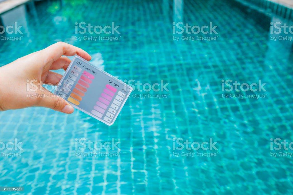 10e4c9c93d0f47 Hand met water testkit testen via de achtergrond wazig zwembad royalty free  stockfoto