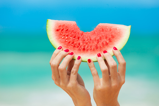 Hand holding watermelon on the beach