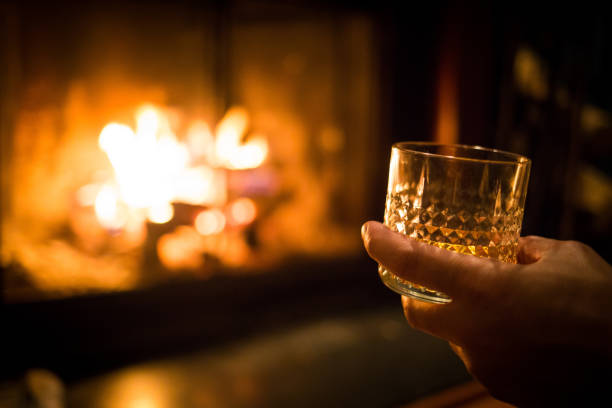 Hand holding whiskey glass at fireplace stock photo