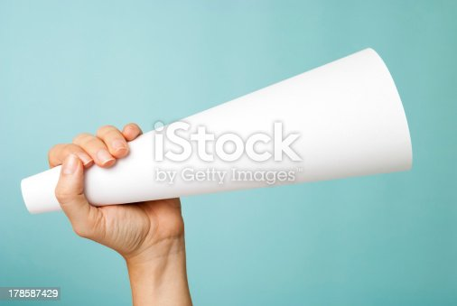 istock Hand holding white blank paper megaphone on blue background 178587429
