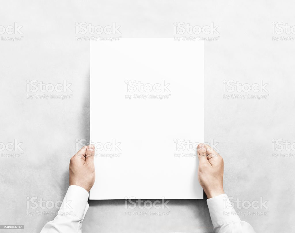 Hand holding white blank poster mockup, isolated. stock photo