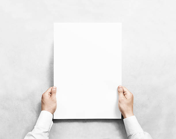 Hand holding white blank poster mockup, isolated. - foto de stock