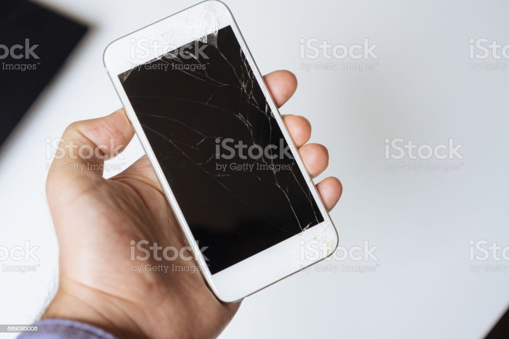 Hand holding white broken phone smashed touch screen stock photo