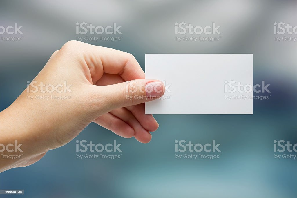 Hand holding white business card on blurred background stock photo